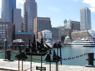 A sculpture of a boat with the harbor and skyscrapers in the background
