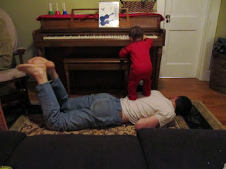 Baby standing on Daddy's back to reach the piano keys