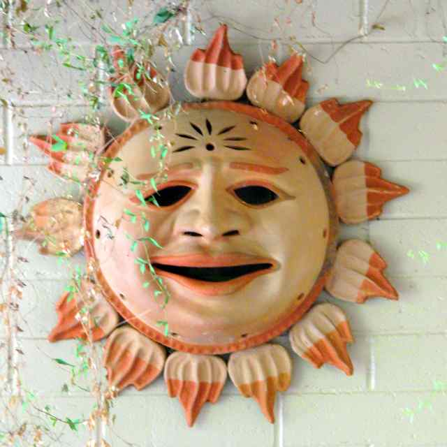Ceramic sun with 13 flames, hung on a wall, with a face bearing a pained expression