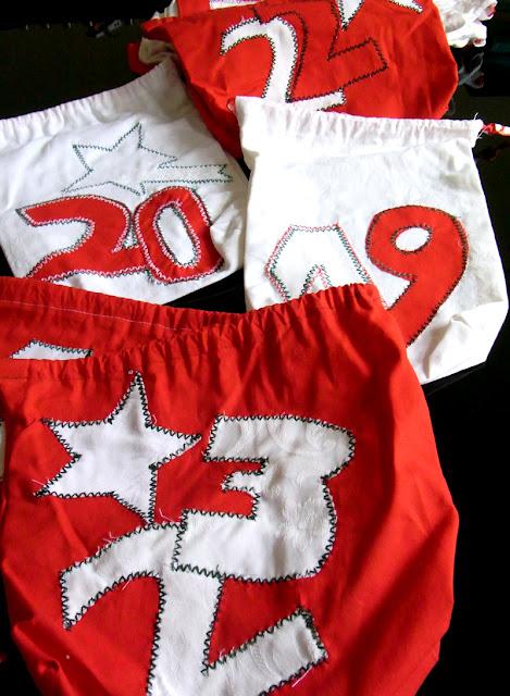 rote und weiße Adventstaschen mit Zahlen und Sternen, aus Damast-Bettwäsche selbst gemacht