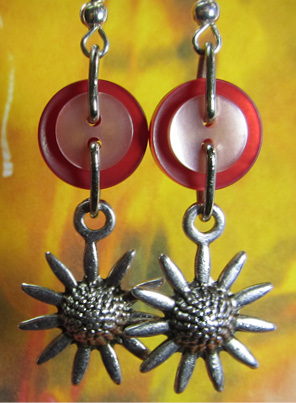 Long earrings have silver sunflower charms hanging from layered red and pink buttons