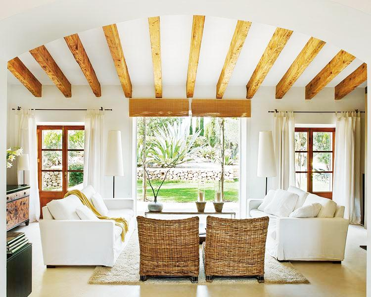 Living room with dueling white sofas, wicker chairs, french doors, a