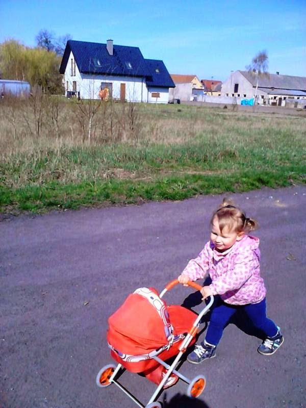 dziewczynka z wózkiem dla lalek na spacerze