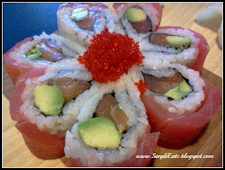 Sushi roll with salmon, avocado topped with tuna and tobiko. Seven sushi pieces shaped like a flower