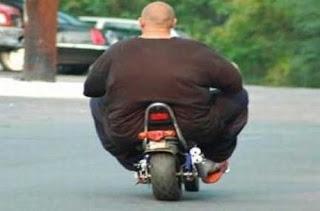 Homem gordo e pequena moto