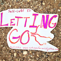 Sign placed on dirt. Sign says Self-Care is letting go. by N. Ortiz www.selfcareforsocialjustice.com