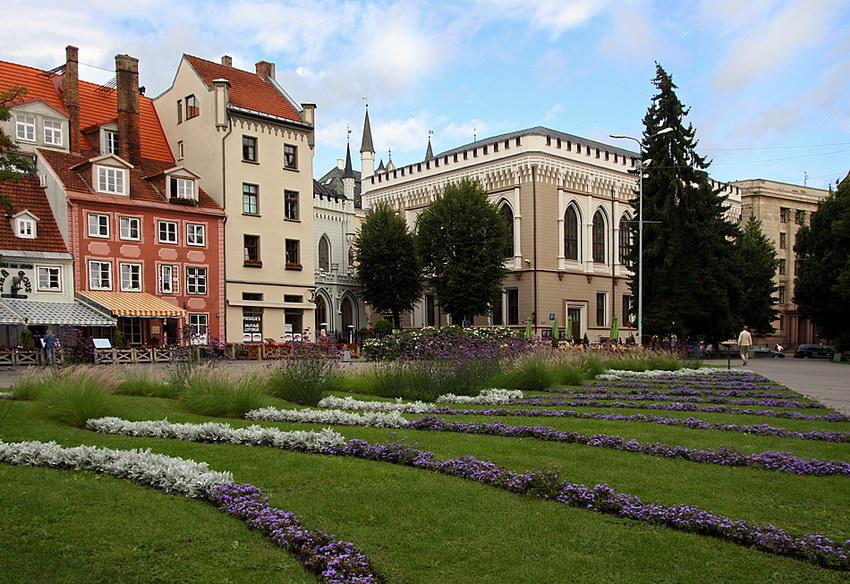 Pormenor da Praça. Jadins relvados em primeiro plano com cordas paralelas de flores e edifícios monumentais ao fundo