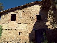 Façana de migdia on s'aprecia el contacte entre les parets de pedra i la tàpia