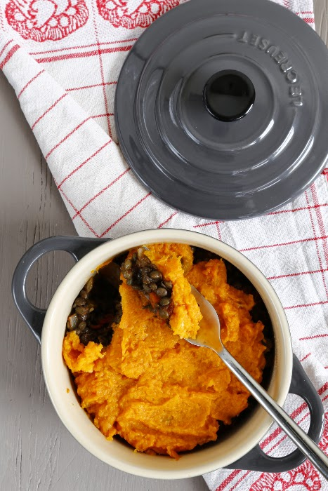 An individual casserole dish layed on a tea towel, filled with a vegetarian shepherd's pie