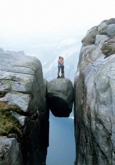 Par omfavner hinanden på stenblokken 'Kjeragbolten' over klippekøft ved Lysefjorden