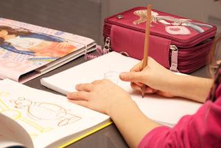 Kind malt mit Dreistöckmäppchen von Topmodel
