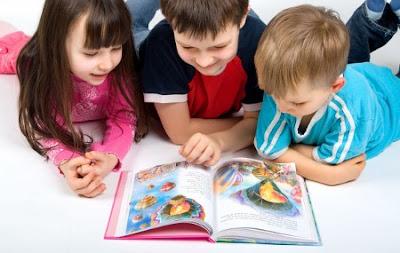 Tres niños leyendo un libro de cuentos