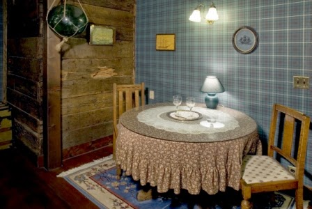 round wood table, wood chairs, blue plaid wall paper, exposed bridge timbers wall