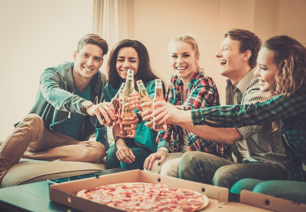 A friend gathering with alcohol and pizza.