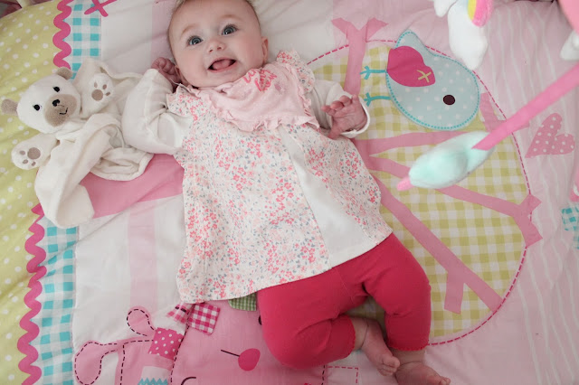 Baby girl wearing dark pink leggings with pink and white long sleeved floral top and pink frill bib