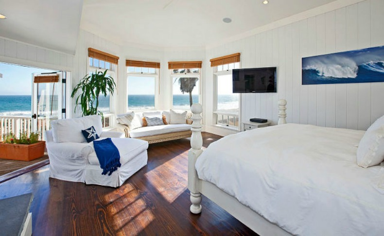 Coastal blue and white beach house master bedroom with slipcover chair and ocean view