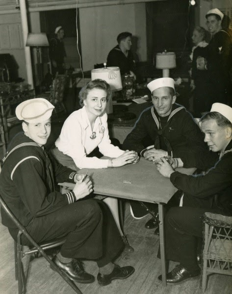 Three sailors sitting at a card table with a young woman.