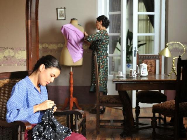 Sira Quiroga cosiendo Madrid con  blusa azul y falda granate. El tiempo entre costuras. Capítulo 1.