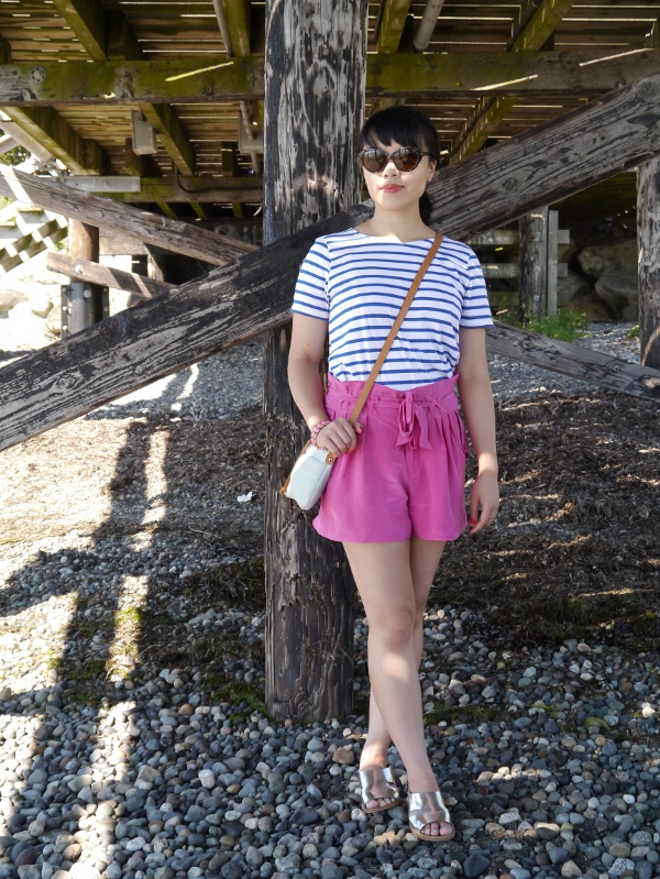 Striped tee worn with fuchsia silk shorts, metallic leather sandals, and a small but colourful crossbody bag and cat-eye shades.