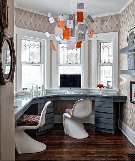 Home office in a bay window nook with built in desk, white Panton chairs, wood floor and trellis wallpaper
