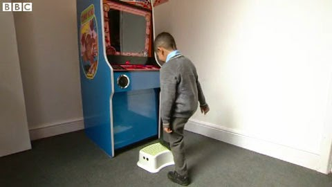 A young boy uses a box to play Donkey Kong