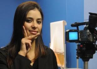 Mulher fazendo sinal em Libras, ao lado de uma câmera de televisão