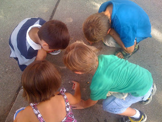 Four kids playing with something on the ground.