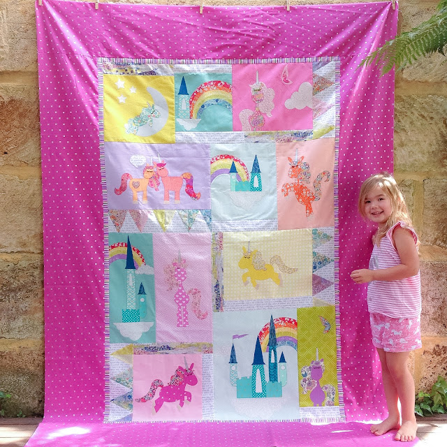 Isla standing next to her new unicorn quilt