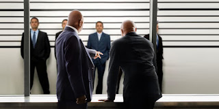 Photo of men looking through a glass partition at a police lineup.