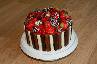 Chocolate and raspberry Kitkat gateau, topped with raspberries and chocolate-dipped strawberries