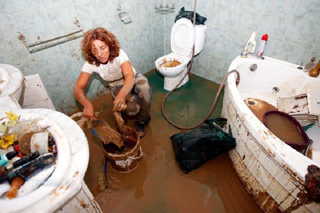 A resident scoops up mud inside her flooded house