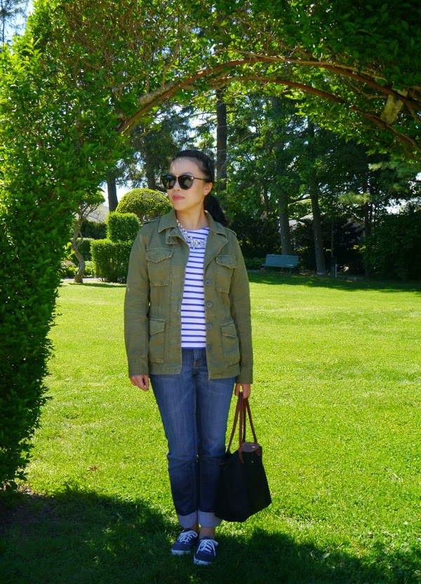 Casual travel style with an army jacket, Breton stripes, jeans, and statement shades and necklace