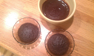 two chocolate cupcakes and a bowl of frosted
