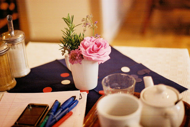 Tabletop with teapot & mug, pens & paper and a vase of flowers.