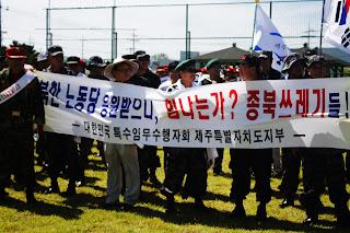 退休海軍在江汀村的遊行,海軍手上拿著的旗幟上寫著:從北的垃圾