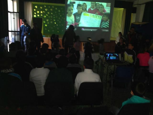 La imagen muestra el salón de actos lleno de niños pequeños una pantalla gigante en el centro