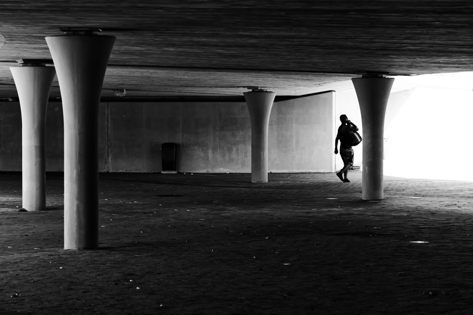 A man walks out of the space under a flyover