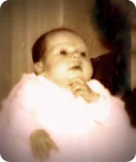 Ich im Alter von fünf Wochen in einem Taufkleid bei meiner Taufe.