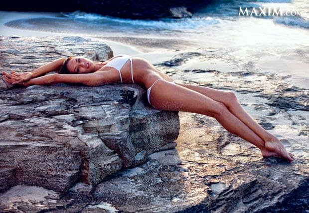 Candice Swanepoel showing off a positively sizzles while dripping sultry on a coastline rock in an emerald white two-piece bathing suit.
