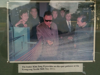 Photo at North Korean Embassy, Phnom Penh, Cambodia: The Leader Kim Jong Il provides on-the-spot guidance at Pyongyang Textile Mill