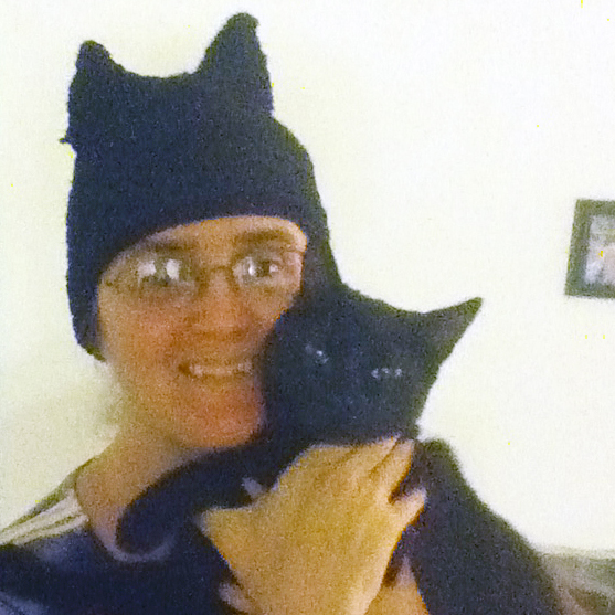 Cynthia M. Parkhill holds her beautiful black cat Starfire close to her face, while wearing her cat ears hat.