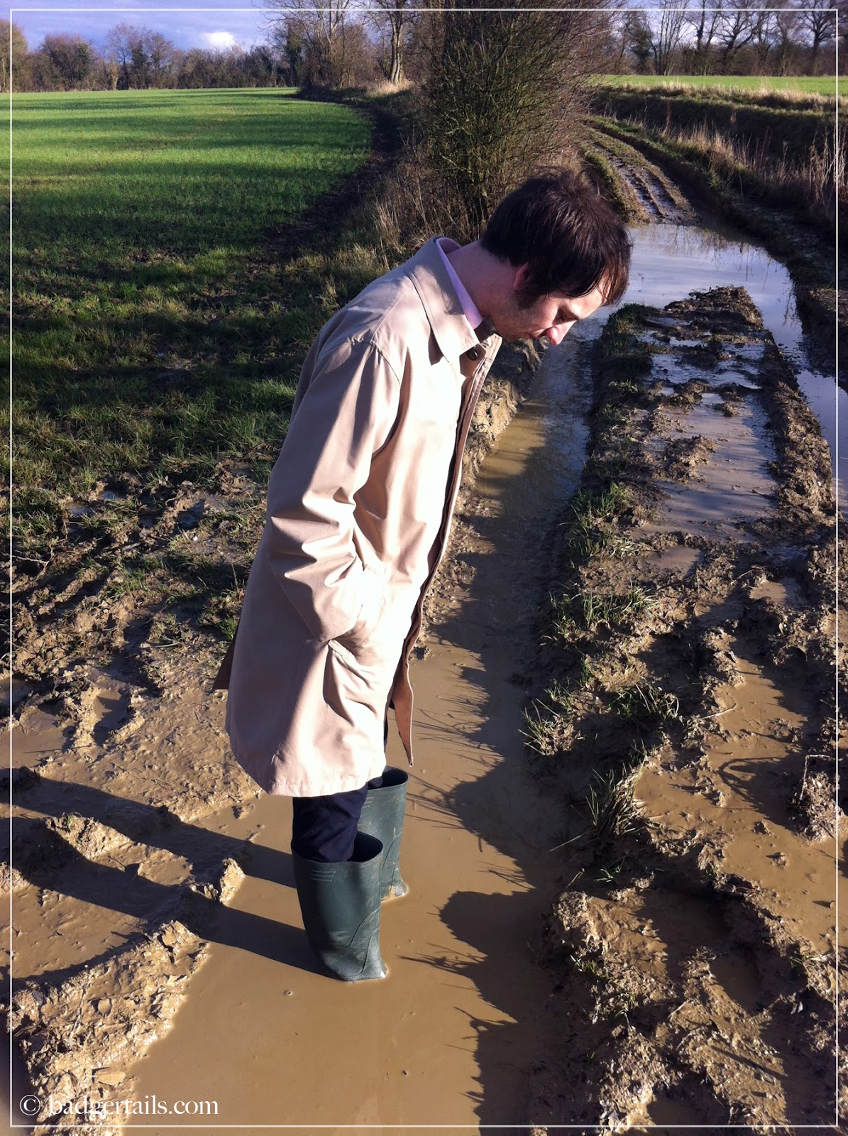 man in wellies and mac stood in puddle