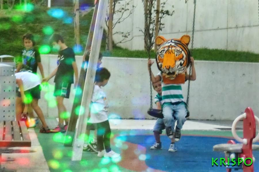 tigre cabezudo de niño columpiándose en parque