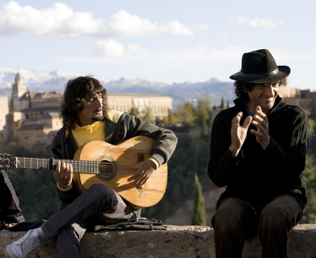 Street performers play guitar and sing in front of the Alhambra at the Mirador de San Nicolas in Granada, Spain.
