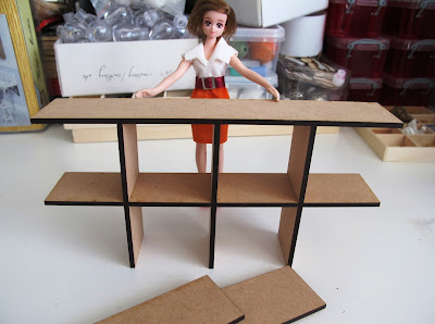 Dry-built modern dolls' house miniature laser-cut 'pidgeon' hole kit  with dolls' house doll for scale.