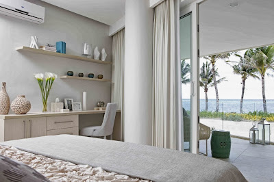a white bedroom facing floor to ceiling window and doors for sea view