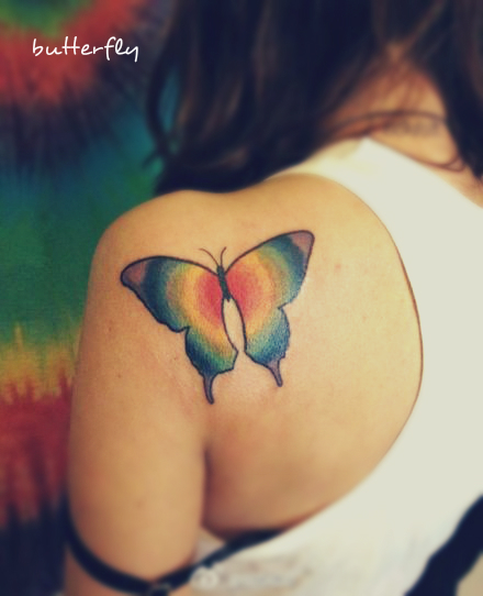 a butterfly tattoo on the back with colors of rainbow