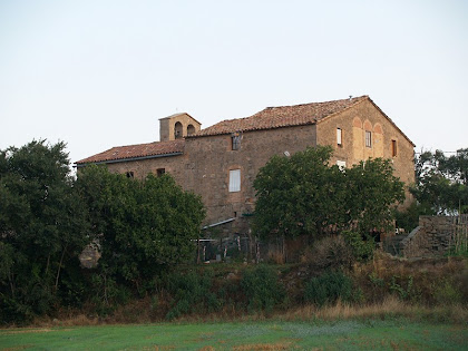 La masia de Cal Fuster adossada a la façana de llevant de l'església