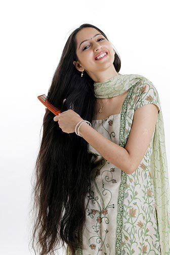 Malayali women combing her long hair.