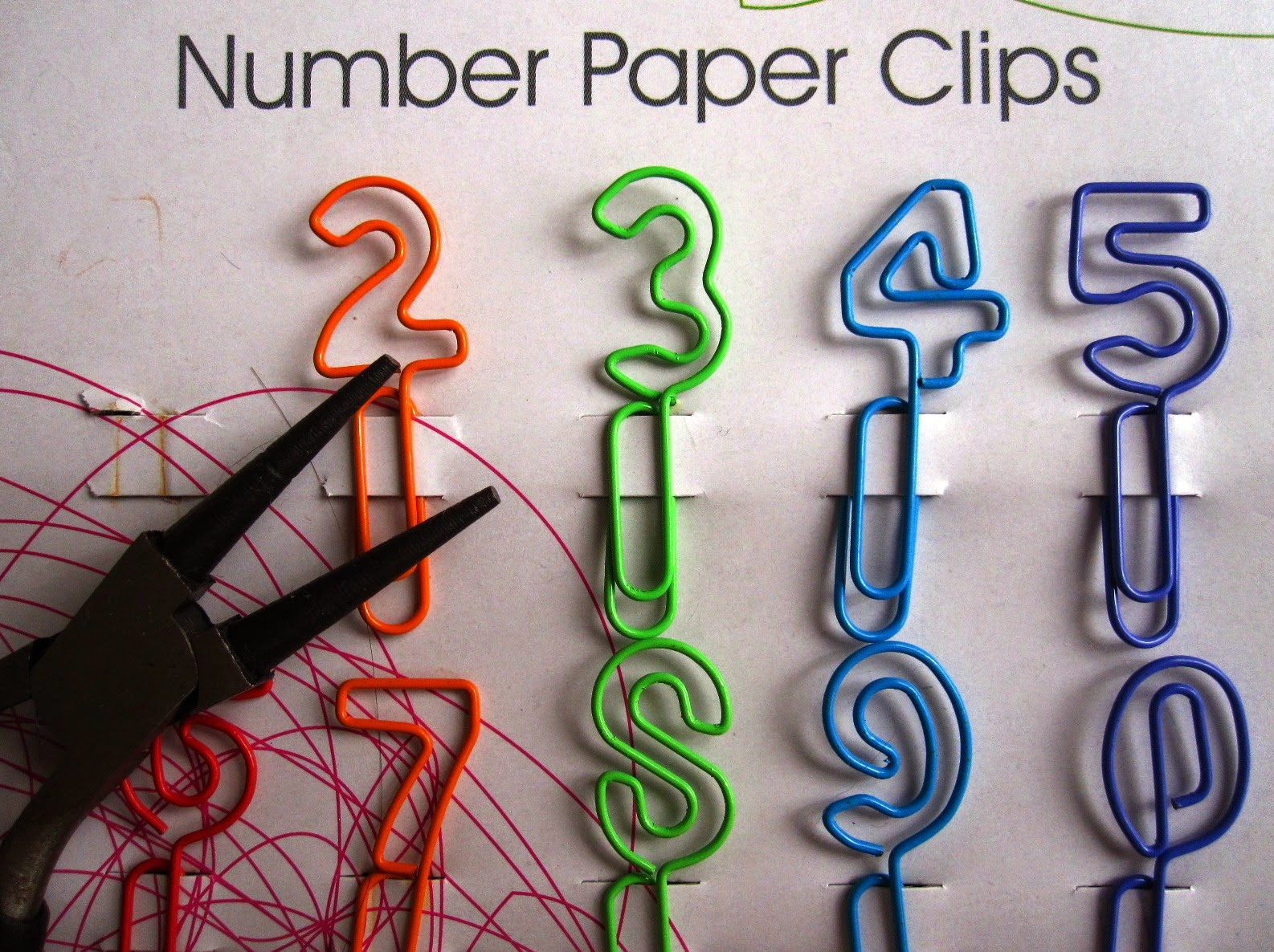 Packet of colourful wire number paperclips with a pair of pliers.